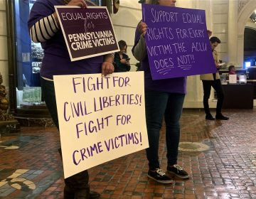 Supporters of Marsy's Law held signs in protest during the ACLU's press conference announcing its lawsuit. (Katie Meyer/WITF)