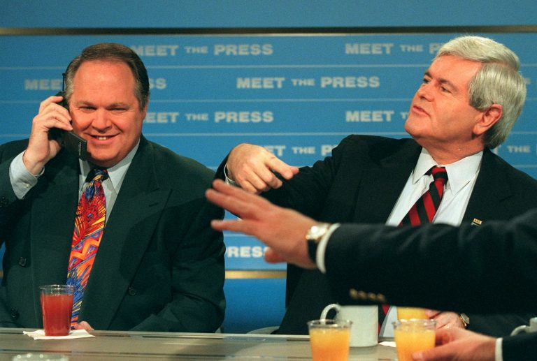 Radio talk show host Rush Limbaugh talks on a phone as House Speaker Newt Gingrich gestures during a break in taping of NBC's