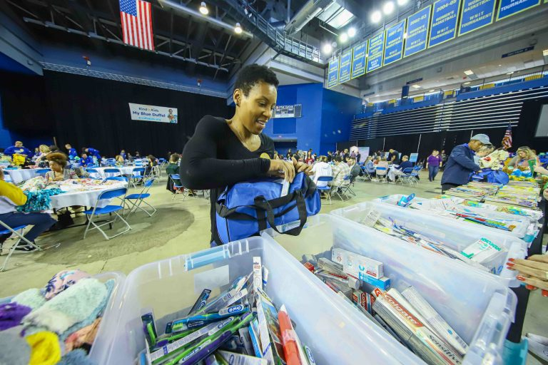 Volunteer Nina Parker packs a duffel full of supplies during Kind to Kids Foundation's 4th Annual My Blue Duffel Community Service Day. (Saquan Stimpson for WHYY)