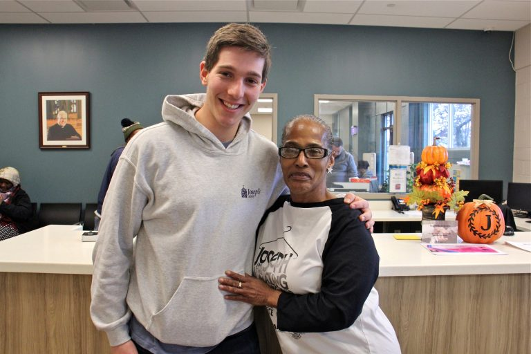 Rutgers-Camden student Nitan Shanas embraces Joseph's House client and volunteer Liz Holmes in the lobby of the Camden homeless shelter where they met. (Emma Lee/WHYY)