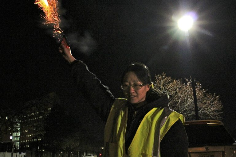 USDA Wildlife Biologist April Simnor uses pyrotechnics to disperse crows in the parking lot behind New Jersey state government offices on West State Street in Trenton. (Emma Lee/WHYY)