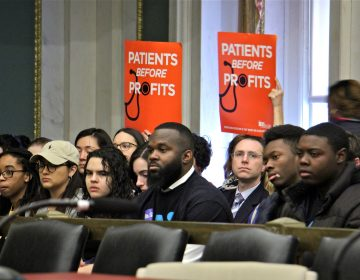 Supporters of a bill that woulf require hospitals to submit a closure plan before shutting down hold up signs during a hearing at City Hall. (Emma Lee/WHYY)