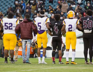 Members of the Camden Panthers and the Pleasantville Greyhounds link arms during a moment of silence for 10 year-old, Micah Tennant, who was shot during a high school football game last week. The game resumed Wednesday at Lincoln Financial field. (Kimberly Paynter/WHYY)