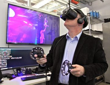 Nick Jushchyshyn, Program Director of Virtual Reality; Immersive Media at Drexel University, watches a dance performance using a virtual reality headset at the school's new Immersive Research Lab. (Emma Lee/WHYY)