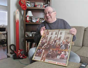 Robert DiBenedetto holds a photo of himself working Philadelphia's Thanksgiving Day Parade in the early 1980s. (Emma Lee/WHYY)