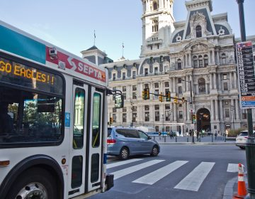 SEPTA buses are given a few seconds ahead of regular traffic to turn, denoted by a vertical white line, at City Hall in Philadelphia. (Kimberly Paynter/WHYY)
