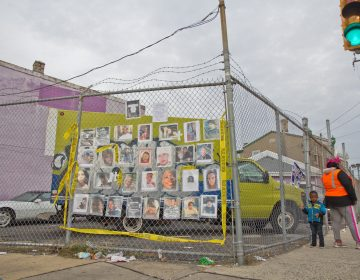 Ros Pichardo, an activist with Operation Save Our City, hung the photos of other victims of gun violence across from the spot where 10 year-old Semaj O'Branty was shot in the head walking home from school Wednesday. (Kimberly Paynter/WHYY)