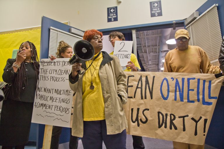South Philly resident Carol White and other members of Philly Thrive block the entrance to a public meeting about the refinery Thursday evening. (Kimberly Paynter/WHYY)