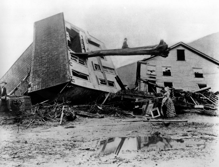 In this historical photo from May 31, 1889, survivors stand by homes destroyed when the South Fork Dam collapsed in Johnstown, Pa. As officials prepare to commemorate the 125th anniversary of the enormous Johnstown Flood of 1889 that killed 2,209 people, new research has helped explain why the deluge was so deadly. (AP Photo)