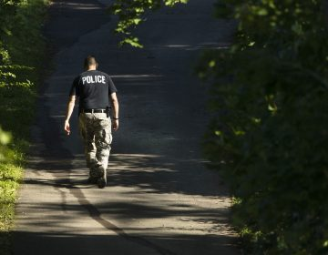 An officer walks up a blocked off drive way, in, Solebury, Pa., as the search continues Wednesday, July 12, 2017, for four missing young Pennsylvania men feared to be the victims of foul play. (AP Photo/Matt Rourke)