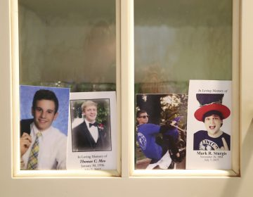 In this Monday, July 2, 2018 photo, four photos, from left, of Jimi Patrick, Tom Meo, Dean Finocchiaro, and Mark Sturgis are placed in a kitchen cabinet window in the home of the grandparents of Patrick, nearing the anniversary of the murders of the four young men in Bucks County in July 2017. Cosmo DiNardo and his cousin Sean Kratz, both 21, were charged in the killings the next day, July 14. (David Swanson/The Philadelphia Inquirer via AP)