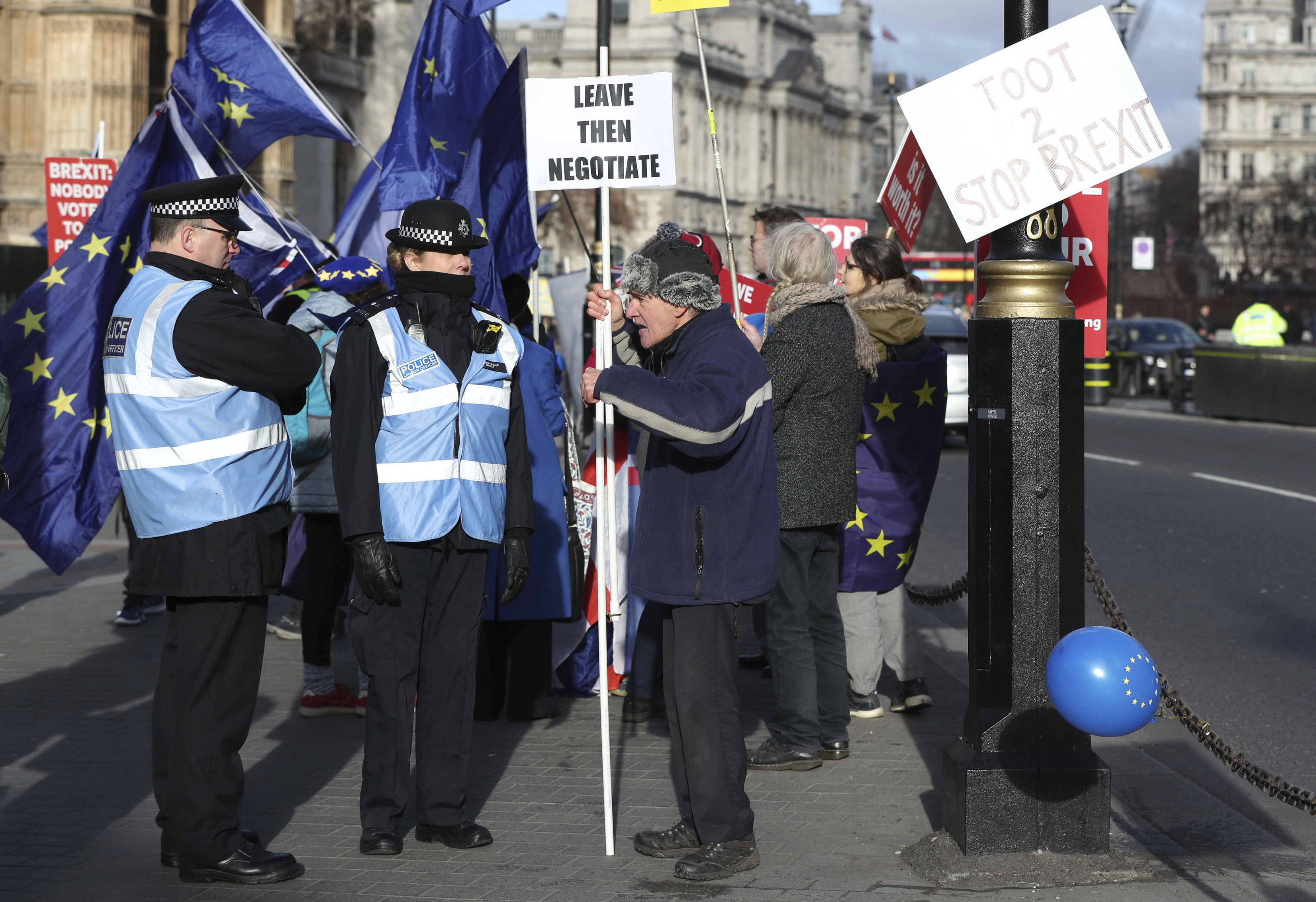 A protester argues with police liaison officers outside Parliament in London, with police briefed to keep law and order in the area, as various Brexit protesters demonstrate in London. Now in the U.K., it's more common to see police liaison officers, who wear blue vests and specialize in communicating with protestors. (Jonathan Brady/PA via AP)