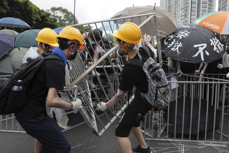 Protesters with umbrellas use steel barricades to block a road as they march through Sha Tin District in Hong Kong. (Kin Cheung/AP Photo)