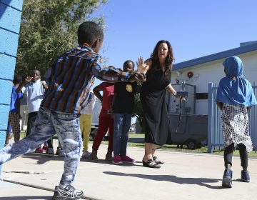 Director Lynette Faulkner, middle, tries to slow down a student at Valencia Newcomer School between classes, in Phoenix. (Ross D. Franklin/AP Photo)
