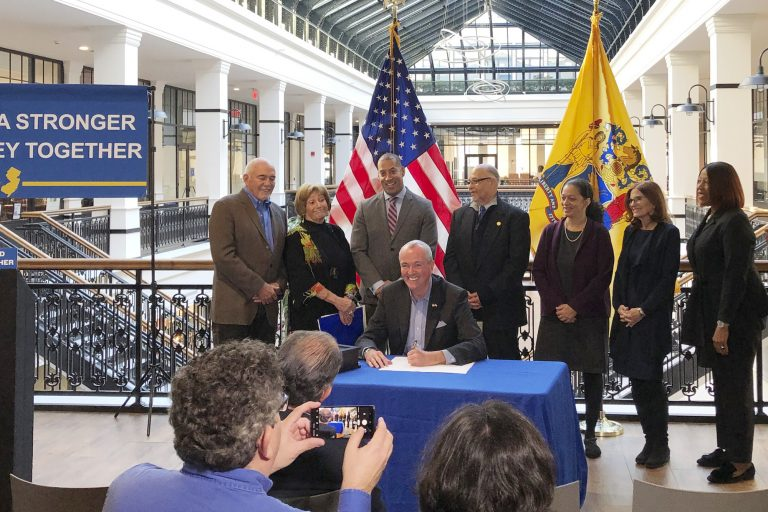Democratic Gov. Phil Murphy signs an executive order creating a board to look into setting up a state-run bank, alongside labor and other supporters, Wednesday, Nov. 13, 2019 in Newark, N.J. New Jersey would be the second state after North Dakota with a state-run bank if Murphy's campaign promises comes to pass. (Michael Catalini/AP Photo)