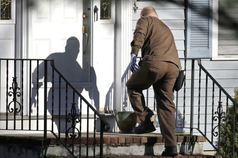 In this Nov. 26, 2019, file photo a UPS man delivers an Amazon package to a residence in North Andover, Mass. Amazon, Walmart and others are promising to deliver more of their goods in a day and this holiday season will be the first real test of whether they can make that happen. (Elise Amendola/AP Photo)