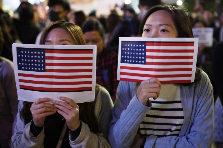 Protester holds U.S. flags during a demonstration in Hong Kong, Thursday, Nov. 28, 2019. China's fury over President Donald Trump's decision to sign legislation supporting human rights in Hong Kong is evident. What's less clear what 'countermeasures' Beijing may take in response to what it said Thursday were 'extremely evil' and dangerous moves. (Vincent Thian/AP Photo)