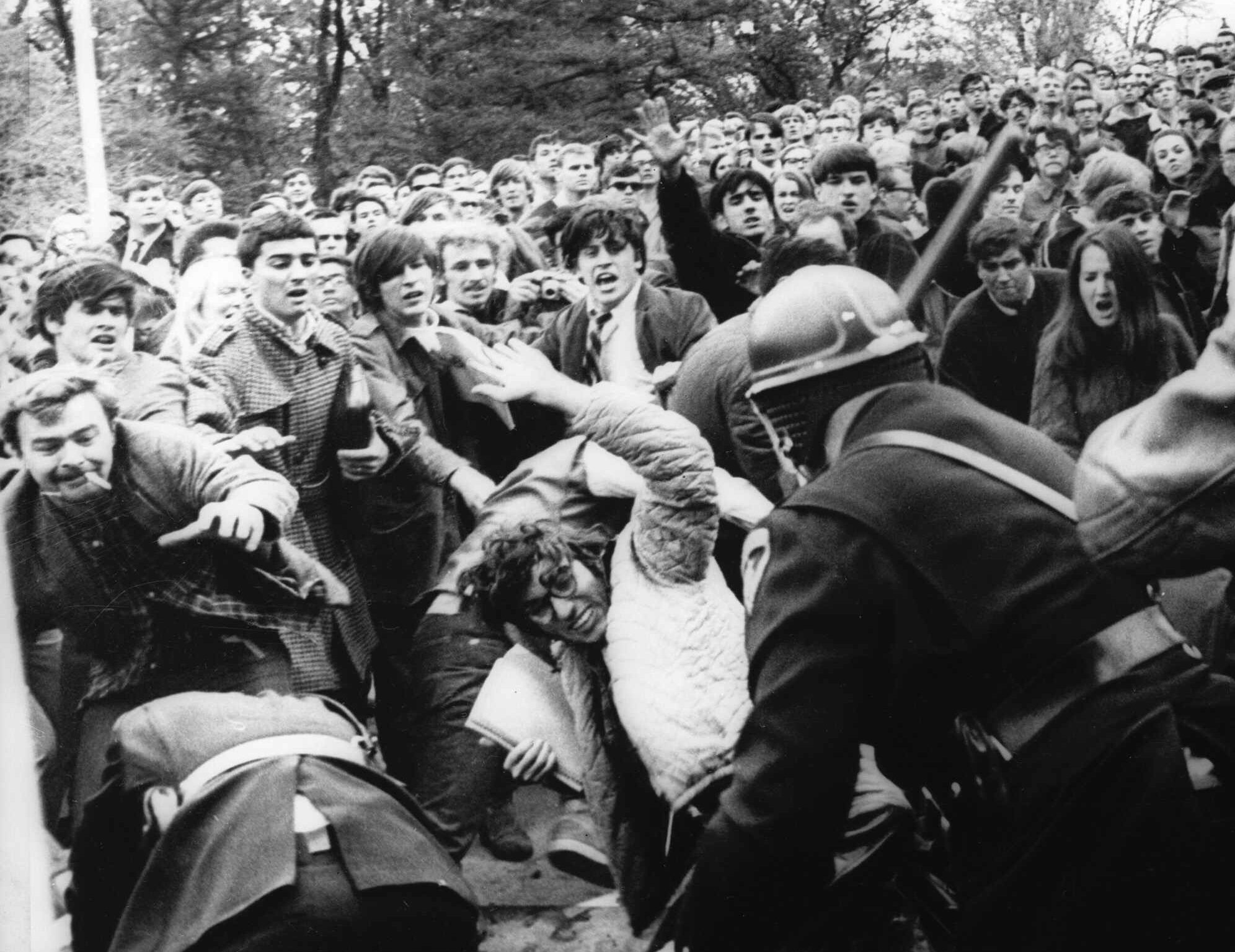 A stick-swinging Madison riot police officer beats back an angry throng of University of Wisconsin protesters, Wednesday, October 19, 1967 on campus. Squads of riot officers broke up a sit-in intended to disrupt the Dow Chemical Company. Dow makes Napalm for the War in Vietnam. (AP Photo)