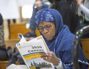 Ruqayya Ali of Center City peruses Philly Counts census literature during the Philly Counts 2020 summit at South Philadelphia High School. (Jonathan Wilson for WHYY)