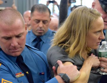 State police remove Sue Altman of New Jersey Working Families from the hearing. (NJ Spotlight)