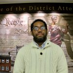 """Formerly incarcerated artist James """"Yaya"""" Hough stands in front of a mural at the Philadelphia District Attorney's Office. (Emma Lee/WHYY)"""