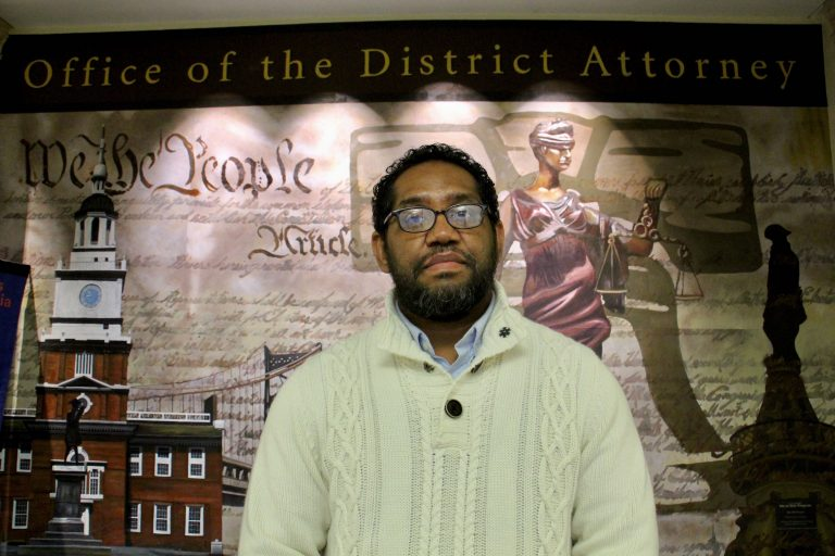 "Formerly incarcerated artist James ""Yaya"" Hough stands in front of a mural at the Philadelphia District Attorney's Office. (Emma Lee/WHYY)"