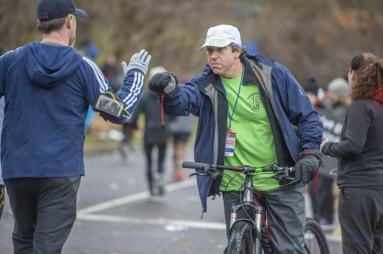At the 18 mile mark, Mitchell Greene fist bumps a runner during the 2019 Phialdelphia Marathon. (Jonathan Wilson for WHYY)