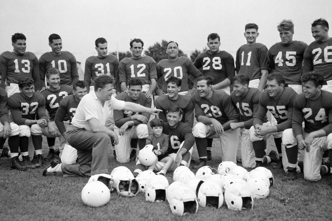 In this July 26, 1939, file photo, Philadelphia Eagles owner and head coach Bert Bell talks to his squad as his son, Bert Bell Jr. sits on a players lap, in Philadelphia. Bell, who later became the league's commissioner, created the NFL draft as a way to assist teams who couldn't attract top talent in the free-for-all system that had been in place. (AP Photo/File)