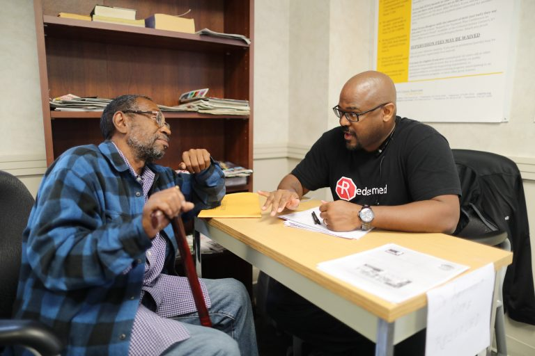 Bill Cobb of Redeemed PA talking with Louis Benson about his right to vote in the Defender Association lobby on Sept. 29, 2016. (David Swanson/The Philadelphia Inquirer)