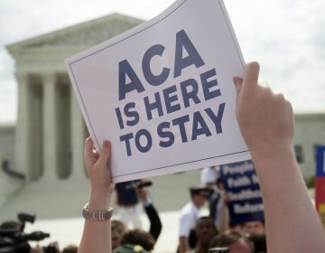 A demonstrator celebrated outside the U.S. Supreme Court in 2015 after the court voted to uphold key tax subsidies that are part of the Affordable Care Act. But federal taxes and other measures designed to pay for the health care the ACA provides have not fared as well. (Andrew Harrer/Bloomberg via Getty Images)