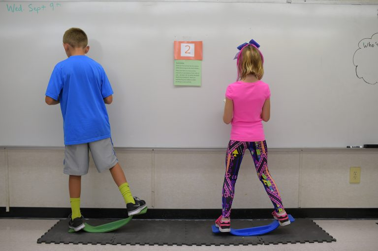 Two fourth-graders rock side to side while doing math equations at Charles Pinckney Elementary School's