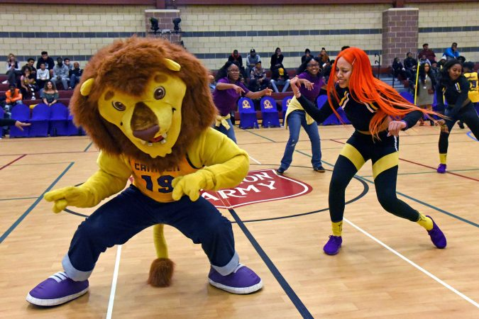 At a November 10 game against the Jersey Express, Camden Monarch dance captain Tina Baker with the team mascot. (April Saul for WHYY)