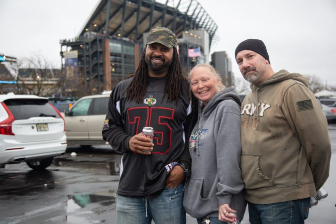 James Whiteside (left) served in the Army from 1993 until 2001. He started coming to the Army-Navy Game when his friends, Danielle and Tom Dologos, gifted him with tickets a few years back. (Emily Cohen for WHYY)
