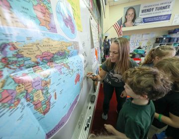 Teacher Wendy Turner writes down notes on the whiteboard during a global awareness session at Mount Pleasant Elementary School in Wilmington. (Saquan Stimpson for WHYY)