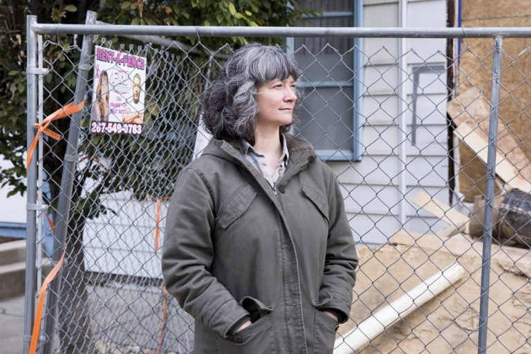 Sara Gallo stands between her home and the new construction next door on November 5, 2019. Due to the demolition and rebuilding of the twin house adjoining hers, her home now suffers structural issues, settling, and leaking. (Rachel Wisniewski for WHYY)