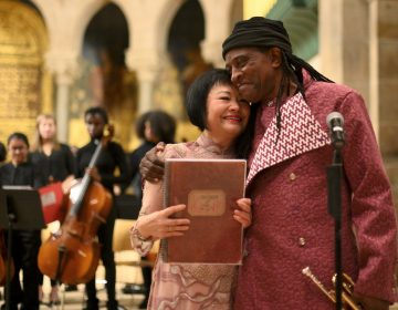 Dr. Kim Phuc and composer Hannibal Lokumbe hug during a concert that includes Lokumbe's composition