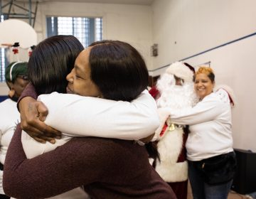 Danielle Shaw (center) embraces a fellow member of Moms Bonded By Grief at a holiday party in South Philadelphia on Dec. 8, 2019. (Becca Haydu for WHYY)
