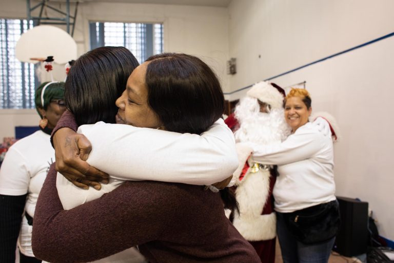 Danielle Shaw (center) embraces a fellow member of Moms Bonded By Grief at the holiday party in South Philadelphia on Sunday. (Becca Haydu for WHYY)