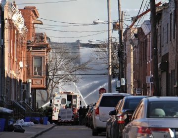 Firefighters pour water on the remains of two rowhouses in the 1400 block of South 8th Street. (Emma Lee/WHYY)