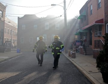 Firefighters walk through a smoke haze on South Beulah Street, checking on residents near the scene of a 3-alarm fire in the 1400 block of South 8th Street. (Emma Lee/WHYY)
