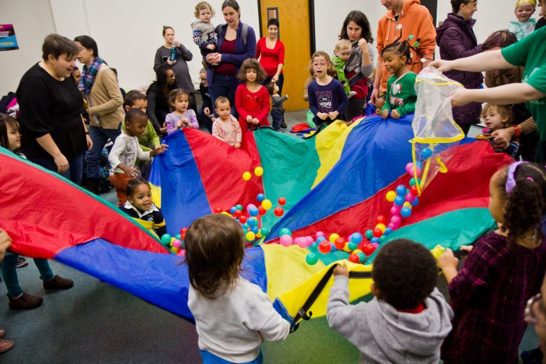 "Kids at the Lucien E. Blackwell West Philadelphia Regional Library celebrate ""Noon Year's Eve"" by playing with a parachute. (Kimberly Paynter/WHYY)"