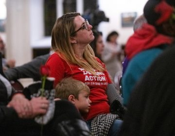 Joyce Pickles of Moms Demand Action sits with her son Dominic, 6, during a vigil for gun violence victims at Broad Street Ministry on Wednesday, December 11, 2019. (Kriston Jae Bethel for WHYY)