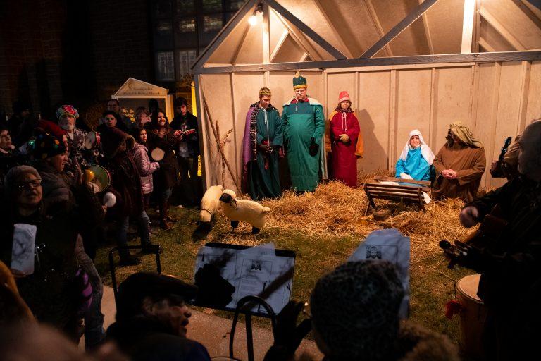 A parranda sings Christmas carols in front of a live nativity at Conshohocken United Methodist Church in Conshohocken, Pa. (Kriston Jae Bethel for WHYY)