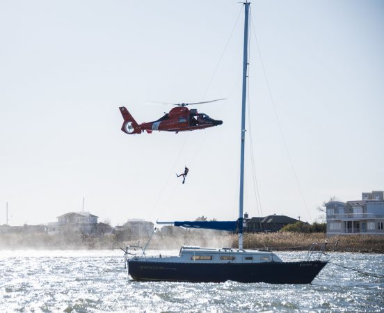 A rescue diver descends from a U.S. Coast Guard helicopter during SERE training. (U.S. Air Force photo by Senior Airman Ariel Owings)