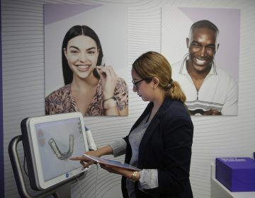 Dental assistant Jessica Buendia looks at a scanned image of patient's teeth in SmileDirectClub's SmileShop. (Jae C. Hong/ AP Photo)