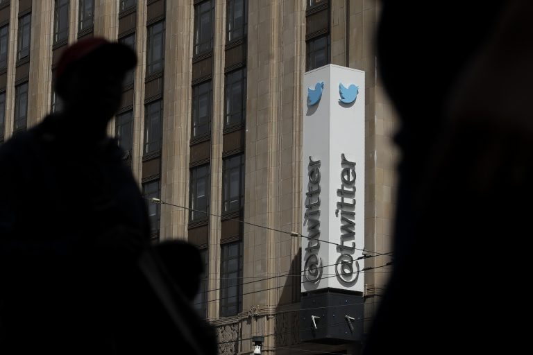 Pedestrians walking across the street from the Twitter office building in San Francisco. (Jeff Chiu/AP Photo)
