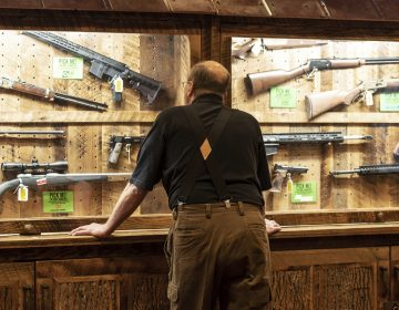 In this April 25, 2019, file photo, a man looks at cases of firearms in the halls of the Indianapolis Convention Center where the National Rifle Association will be holding its 148th annual meeting in Indianapolis. The number of background checks conducted by federal authorities is on pace to break a record by the end of this year. (Lisa Marie Pane/AP Photo)
