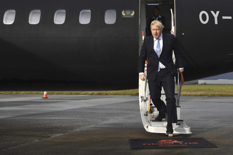 Britain's Prime Minister Boris Johnson arrives at Cardiff Airport while on the General Election campaign trail in Wales, Wednesday, Dec. 11, 2019. Britain goes to the polls on Dec. 12. (Ben Stansall/Pool Photo via AP)