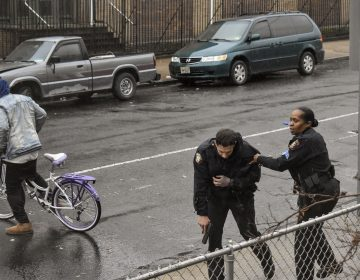 Jersey City police Sgt. Marjorie Jordan, right, helps fellow officer Raymond Sanchez to safety after he was shot during a gunfight that left multiple dead in Jersey City, N.J. (Justin Moreau/AP Photos)