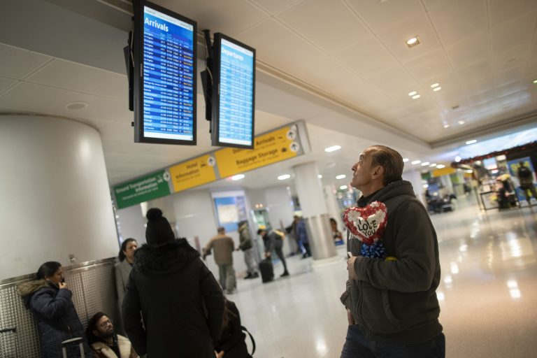 """In this Dec. 3, 2019, photo, Mohammed Hafar checks the arrivals road while waiting for his daughter Jana Hafar's flight at JFK Airport in New York. Mohammed Hafar was part of a federal lawsuit filed in August of this year over the travel ban waiver process. """"Every time I speak to her, she ask, 'When are they going to give me the visa?'"""